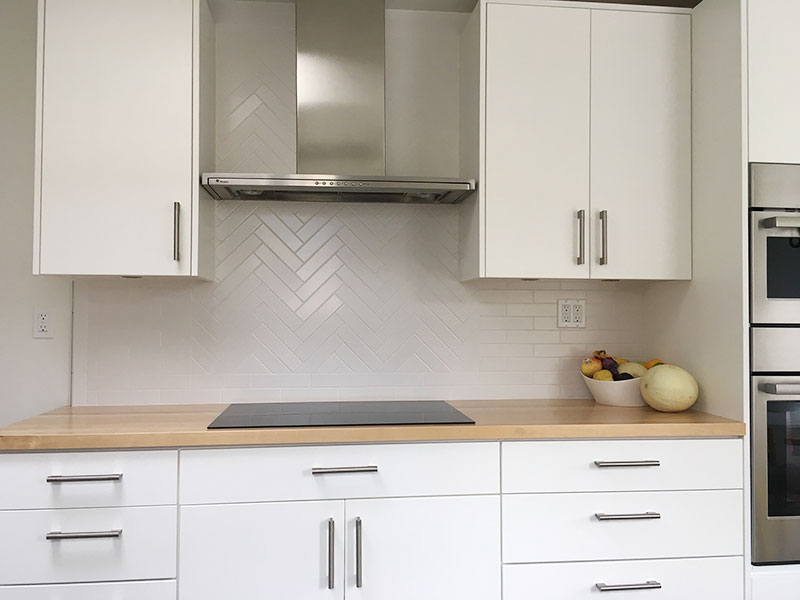 2x8 harringbone and subway tile combination kitchen backsplash behind modern range