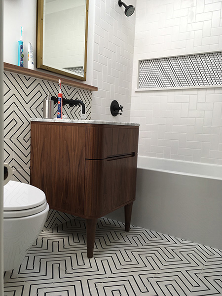 Herringbone tub surround with penny round niche and contrasting grout. Floor and wainscot wall in 8x8 cement tile